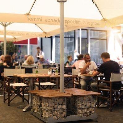 Menschen in Restaurant sitzen unter Gastroschirm Caravita Multicube